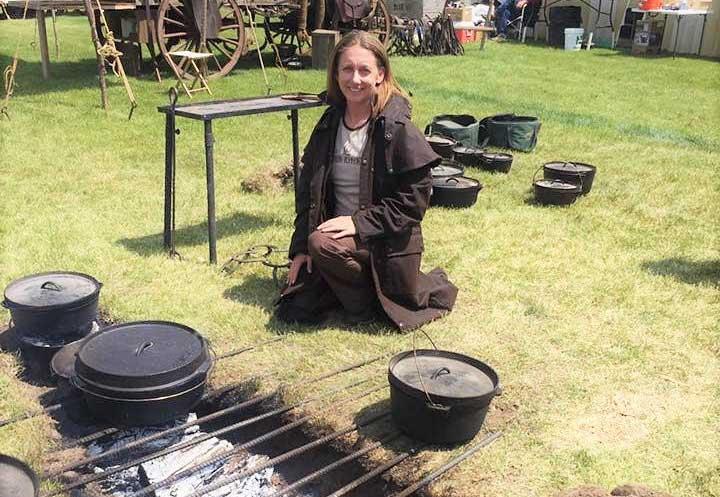 Saffron Hodgson kneeling in front of some dutch ovens