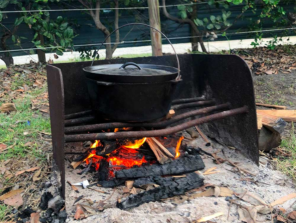 a camp oven over a fire cooking camp oven vegetable stew