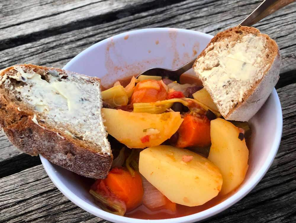 camp oven vegetable stew served in a bowl with bread