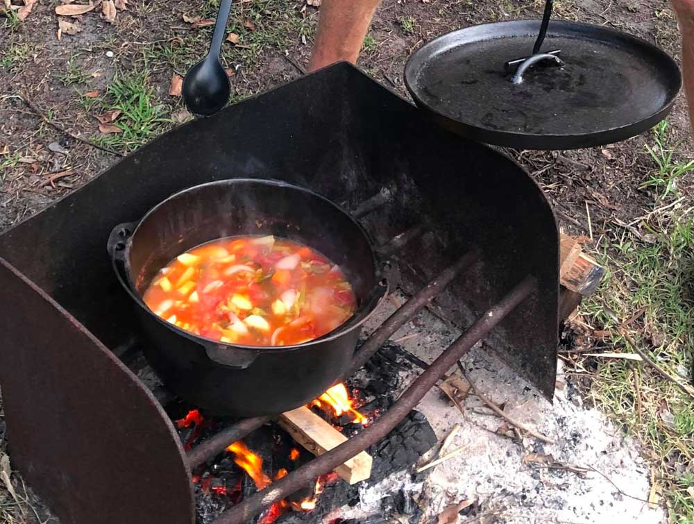 stiring the camp oven vegetable stew